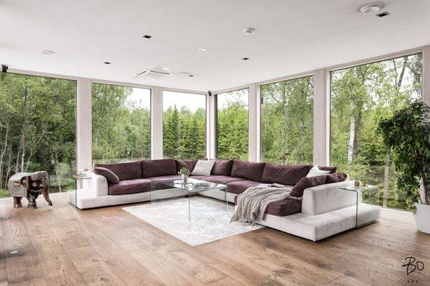 Olohuoneessa on vaikuttavat lasiseinät, joiden takaa näkyy metsää.