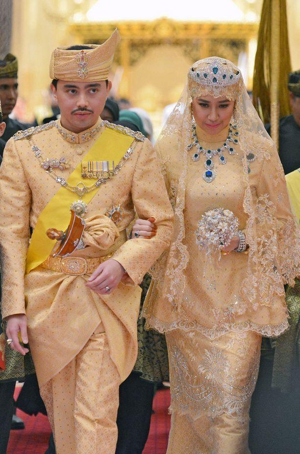 Hääpari oli pukeutunut kullansävyiseen malaijiasuun.