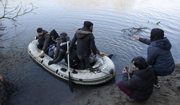 Pakolaisia tulossa Kreikan puolelle sunnuntaina rajajoen yli Edirnessä.