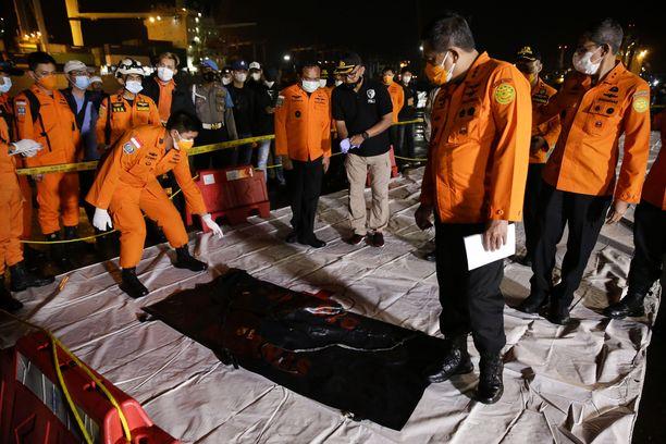 Indonesialaiset pelastusviranomaiset tutkivat laukkua, jossa uskotaan olevan kadonneen koneen osia.
