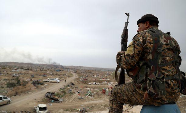 SDF-joukkojen taistelija istui rakennuksen katolla Syyrian Baghuzissa. Pentagonin tuoreen raportin mukaan joukoilla on hankaluuksia toteuttaa operaatioitaan nyt, kun Yhdysvallat on vetänyt joukkonsa alueelta.