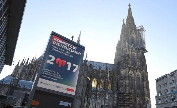 """Kölnin päärautatieaseman edessä on kyltti, jossa lukee vapaasti suomennettuna """"hyvää uuden vuoden alkua"""". Poliisi valvoo aluetta valvontakameroilla, joiden korkealaatuisuutta on saksalaismediassa korostettu."""