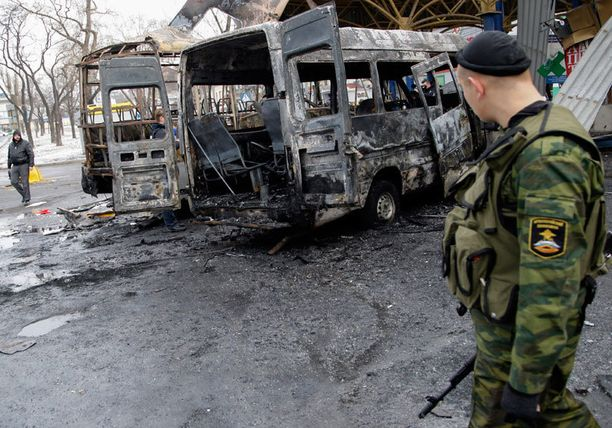 Separatistitaistelija tarkasteli tuhoutunutta bussia Donetskissa.