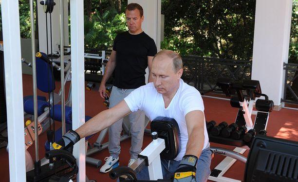 Vladimir Putin vietti urheilullista sunnuntaiaamua elokuussa 2015 Sotshin asunnollaan. Taustalla Venäjän pääministeri Dmitri Medvedev.