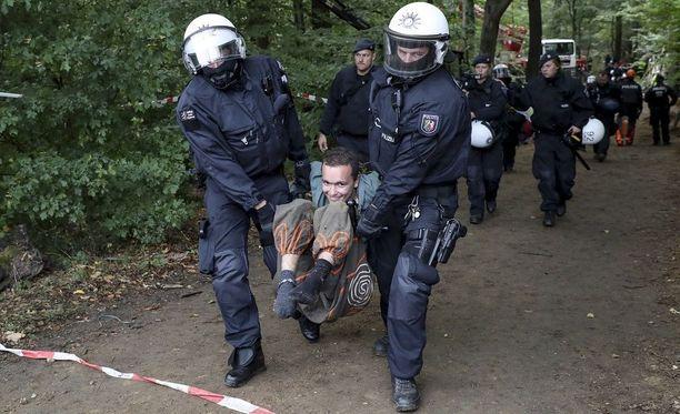 Poliisit kantoivat hiilikaivosta vastustavaa aktivistia Hambachin metsässä torstaina.