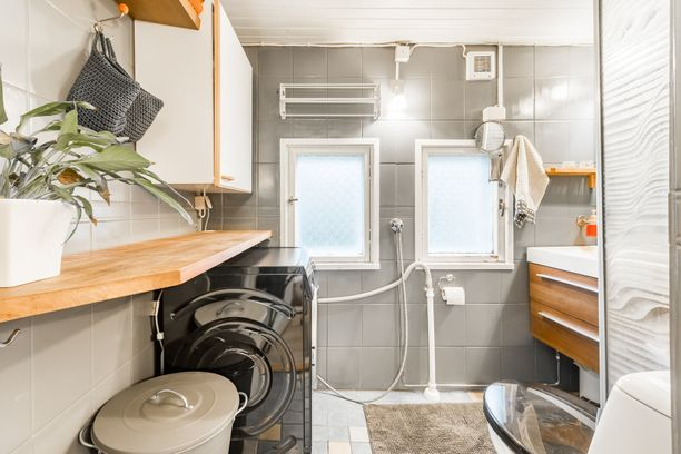 Kylpyhuoneessa on tilaa pesukoneelle ja pyykkikorille. Niiden yläpuolella oleva seinätila on hyödynnetty hyvin muun muassa hyllyjen ja korien avulla.