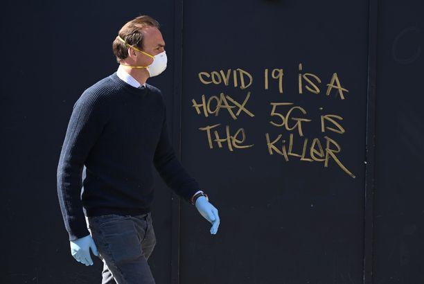 COVID-19 on huijaus, tappaja on 5g, julistaa seinäkirjoitus Lontoossa.