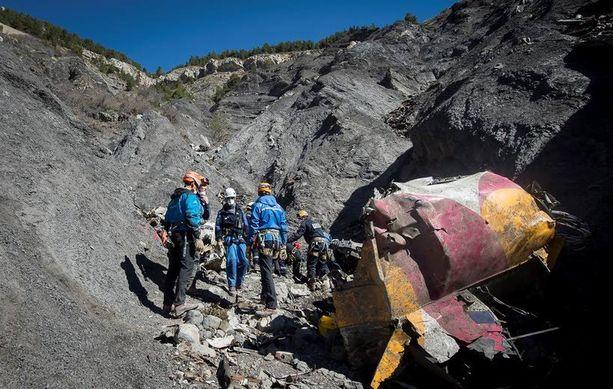 Tiistaina otetussa kuvassa ranskalaiset pelastustyöntekijät seisovat koneen jäännösten vierellä lähellä Ranskan Seyne-les-Alpesia.