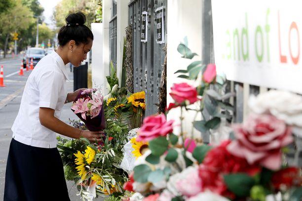 Kuvassa nainen viemässä kukkaa Al Noor moskeijan eteen kuolinuhrien muistoksi Christchurchissa Uudessa-Seelannissa 15.3.2019.