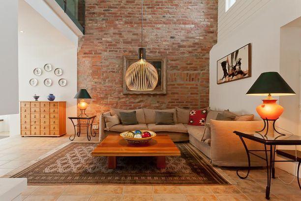 Vanha tiiliseinä on jätetty näkyviin. Seinä tuo luonnetta muuten moderniin tilaan. Huomaa myös, että tiiliseinän värit toistuvat sisustuksessa.