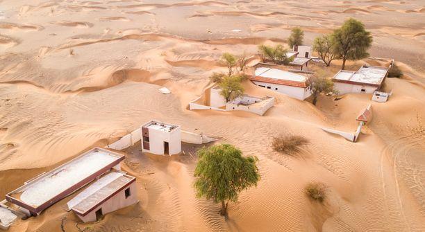 Ilmakuva hiekalla täyttyvästä Al Madamin kylästä.