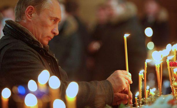 Putin sytytti kynttilän kirkossa.