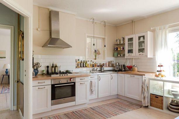Tämä valkoinen keittiö on tyyliltään aiemman vastakohta. Lämmin, kellertävä maali, puutasot ja keittiökaapit tekevät keittiöstä hieman maalaisromanttisen.