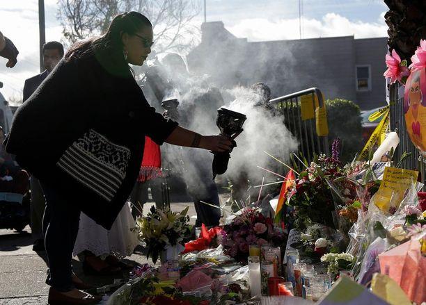Ihmiset ovat tuoneet kukkia ja kynttilöitä varastorakennuksen lähelle Kalifornian Oaklandissa.