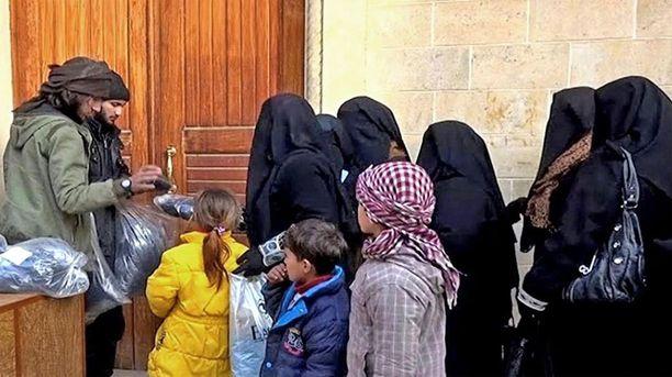 Isis-taistelijat jakoivat naisille huntuja ja niqabeja Mosulissa alkuvuonna 2014.
