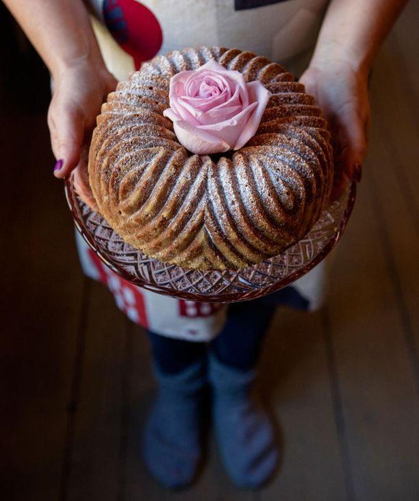 Kakun voi koristella yksinkertaisesti tomusokerilla ja ruusulla.