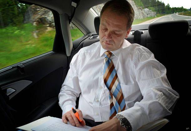 Ministerit voivat hyödyntää matka-ajan työskentelemällä autossa, kuten tässä silloinen elinkeinoministeri Jan Vapaavuori kesäkuussa 2014.