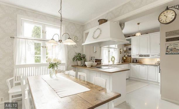 Maalaisromanttisen keittiön tunnelma syntyy muun muassa vaaleista pinnoista, lautalattiasta ja hennosti kuviodusta tapetista.