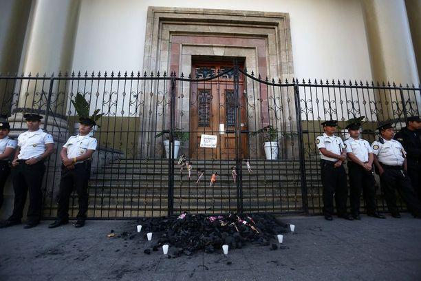 Poliisi valvoi presidentin virka-asuntoa torstaina. Edustalle oli tuotu kasa hiiliä, johon oli laitettu nukkeja.