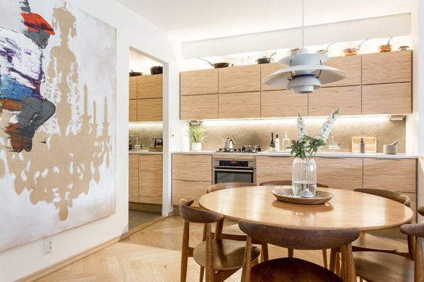 Keittiön minimalistinen muotoilu yllättää kauniilla puupinnalla, joka on mietitty muun kokonaisuuden kanssa yhteensopivaksi.