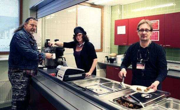 Eija Tuohimaa kaataa kahvia Timo Lindbergille ja Kari Otollinen laittaa lihapullia lautaselle Jyvässeudun Työllistämisyhdistyksen ruokalassa Jyväskylässä.