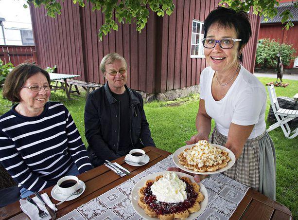 Pirjo Paananen tarjoilee Helena ja Matti Peltoselle vohveleita, joissa höysteenä hilloa sekä omenoita.
