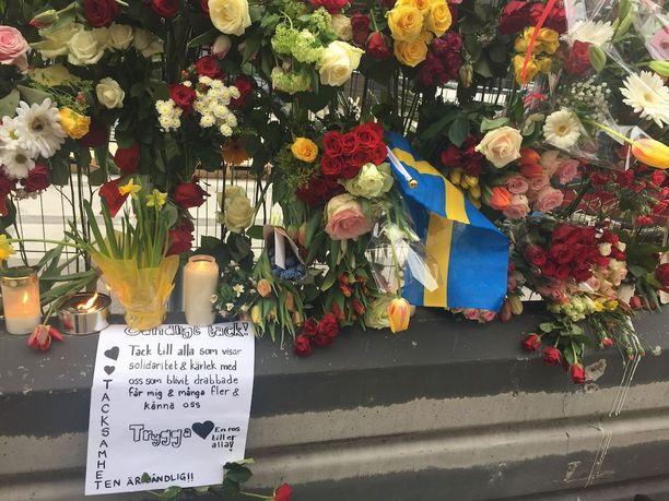 Ihmiset kävivät jättämässä solidaarisuudesta ja rakkaudesta kertovia viestejä Åhlensin edustalle.