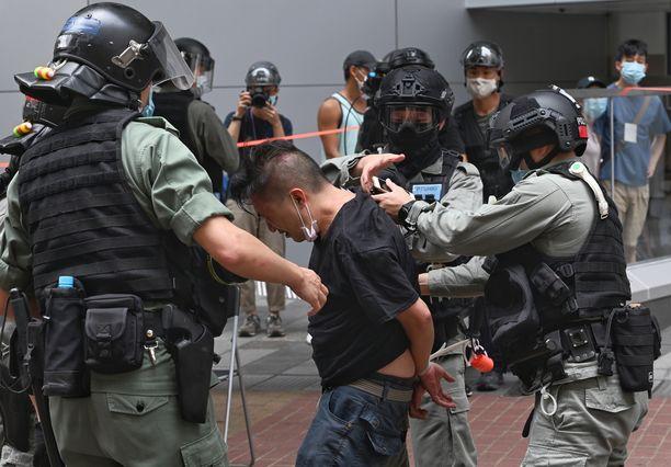 Poliisit pidättävät mielenosoittajan Hongkongissa 1. heinäkuuta.