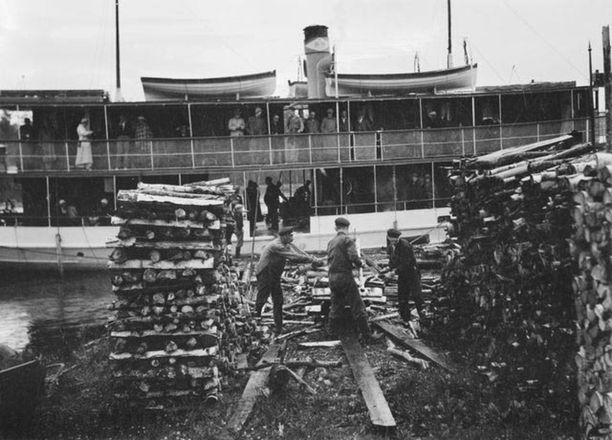 Sisävesilaivan halkovarastoa täydennetään Heinäveden laiturissa. Kuva vuodelta 1936.