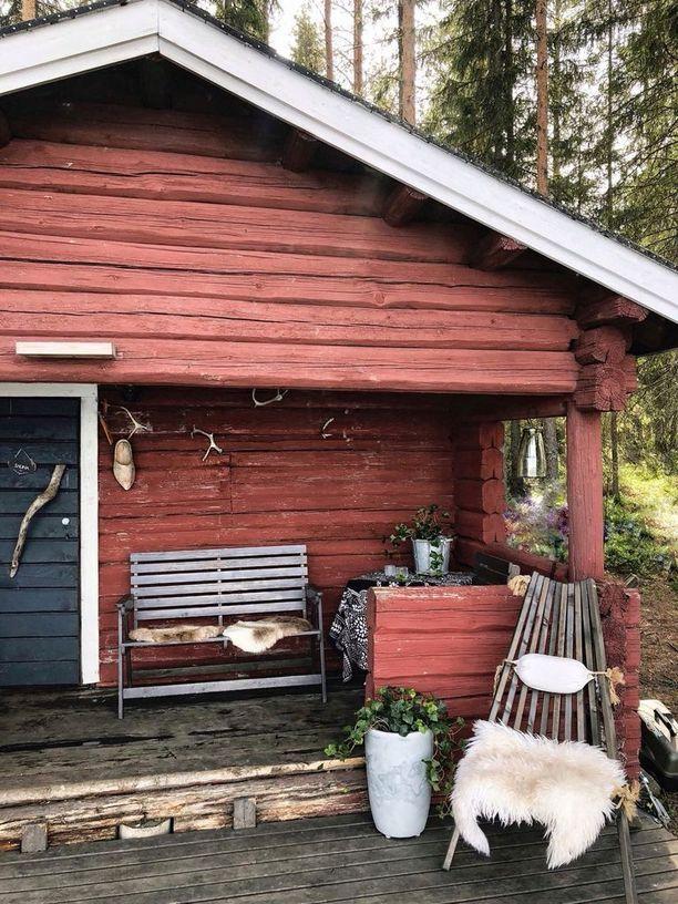 Naulakkoina saunan terassilla on käytetty poronsarvia ja seinää koristaa myös mökiltä löytynyt vanha hollannikas.