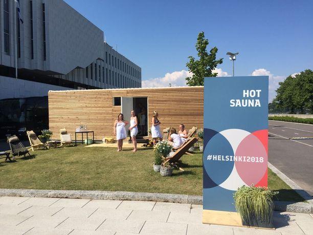 Mediakeskuksessa työskentelevät Outi ja Anne pääsivät suomalaisina näyttämään mallia saunomisessa kansainvälisille toimittajille.