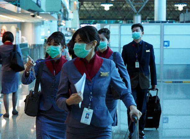 Lentokoneen matkustamohenkilökunnan jäsenet käyttivät hengityssuojaimia torstaina lentokentällä Taiwanissa.