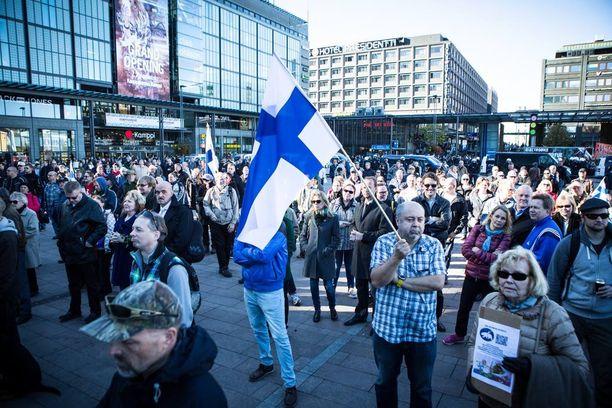 Turvapaikanhakijoita vastustavia mielenosoittajia. Useammalla oli kädessään Suomen lippu.