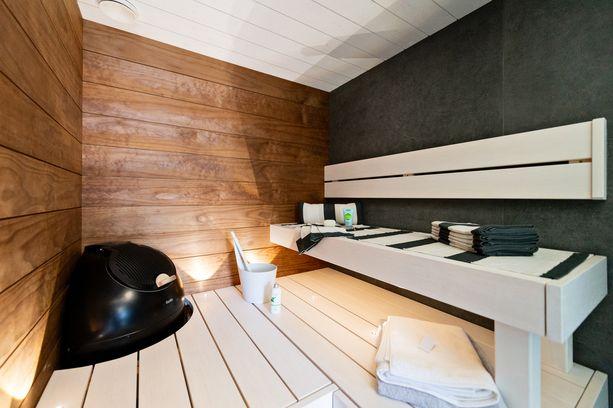 As Oy Porin Villa Sun -kohteen saunassa yhdistyvät kauniisti ruskea, valkoinen ja musta.