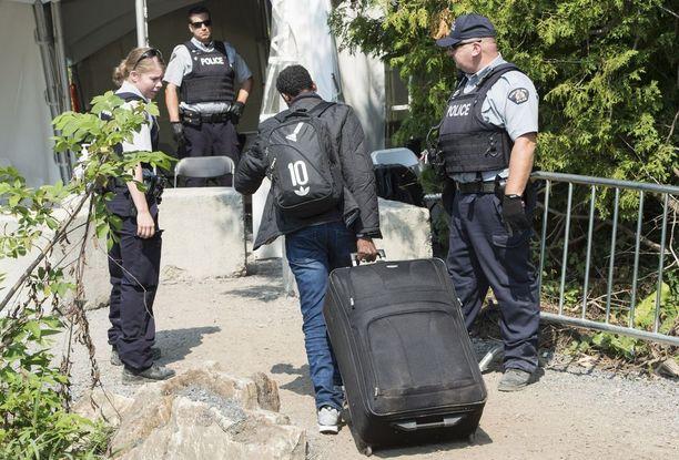 Eritrealainen turvapaikanhakija ylittää Kanadan ja Yhdysvaltojen rajaa New Yorkin osavaltiossa.