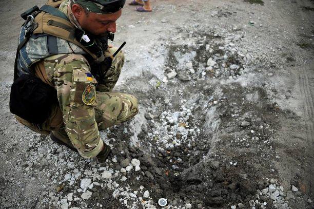 CIMICissä työskentelevä Igor näyttää kompassin avulla, että kranaattituli on tullut idästä Andriivkan kylässä.