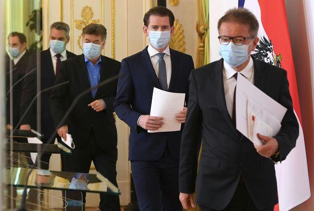 Itävallan liittokansleri Sebastian Kurz (jonossa toisena) marssitti hallituksensa tiedotustilaisuuteen asianmukaisissa hengityssuojissa.