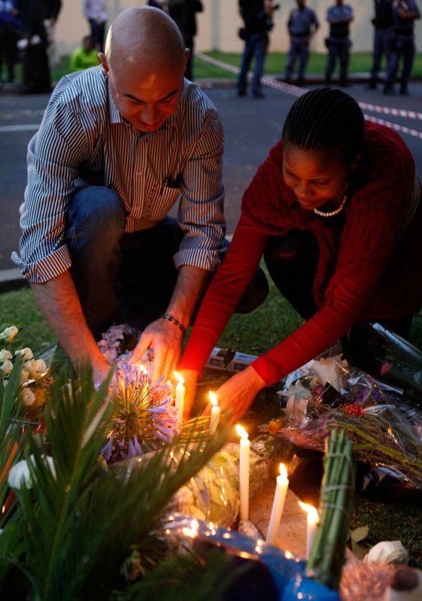 Mies ja nainen sytyttävät kynttilöitä Mandelan muistoksi Mandelan talon edessä.