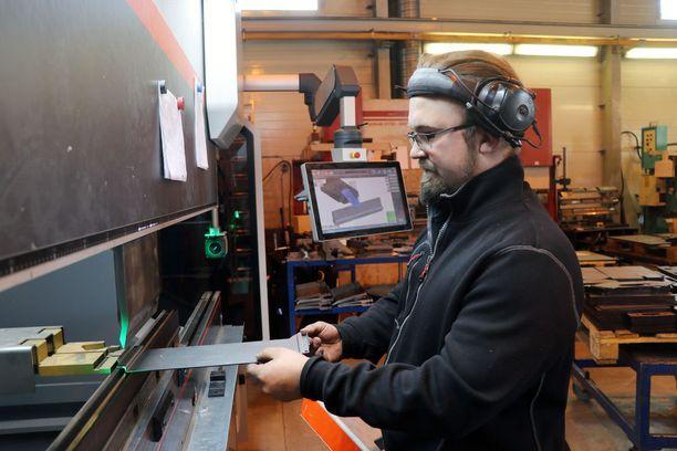 Mikko Virtala taittaa työstetyn metallilevyn haluttuun muotoon ja vertaa sitä kolmiulotteisena pyöriteltävään kuvaan ruudulla.