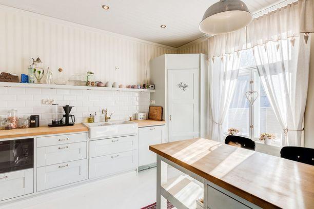 Tässä keittiössä maalaisromanttinen tunnelma on luotu pienin elementein. Yläkaapittomuus keventää keittiön ilmettä. Kaappien tilalla on avohyllyjä, joilla voi asetella kauneinta keramiikkaa ja upeimmat astiat.