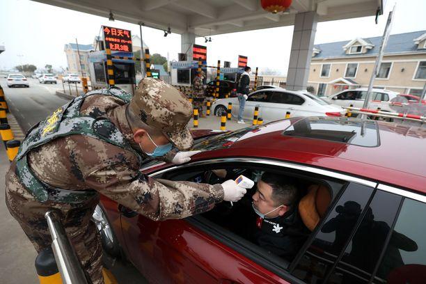 Armeijan edustaja mittasi lämmön kuljettajalta tietullipisteellä Wuhanissa torstaina. Tarkoituksena on estää koronaviruksen leviäminen.
