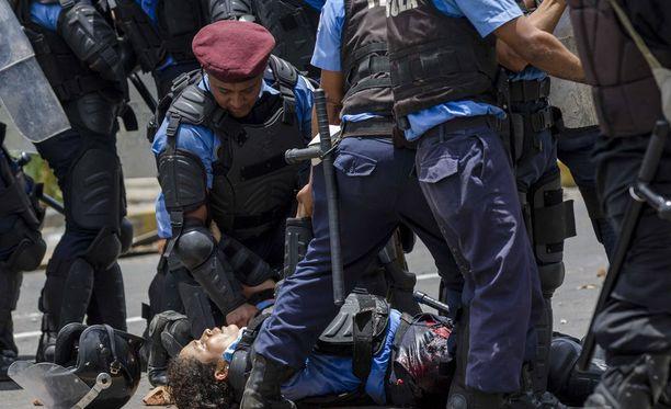 Mellakkapoliisi auttoi haavoittunutta kollegaansa mellakan keskellä.