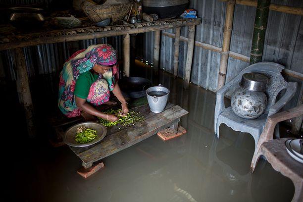 Nainen valmistaa ruokaa kodissaan Bangladeshissa veden noususta huolimatta.