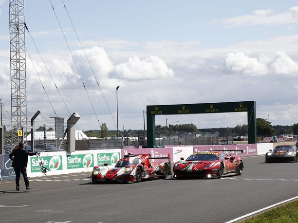 Ruutulippumies oli lähellä jäädä auton alle Le Mans -kisan lopussa.