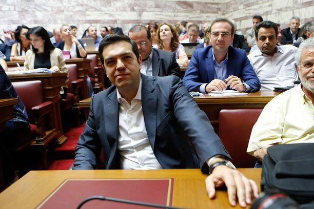 Alexis Tsipras omiensa keskellä keskiviikkona Kreikan parlamentissa Ateenassa.