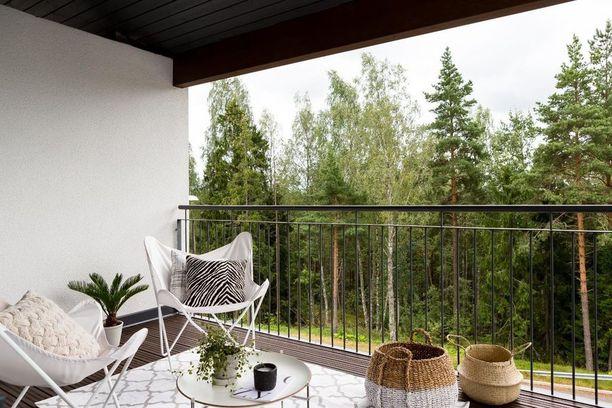 Palmukasvi, seeprakuosinen tyyny ja punotut korit tuovat eksotiikkaa tälle parvekkeelle. Valkoiset lepakkotuolit kutsuvat rentoutumaan.