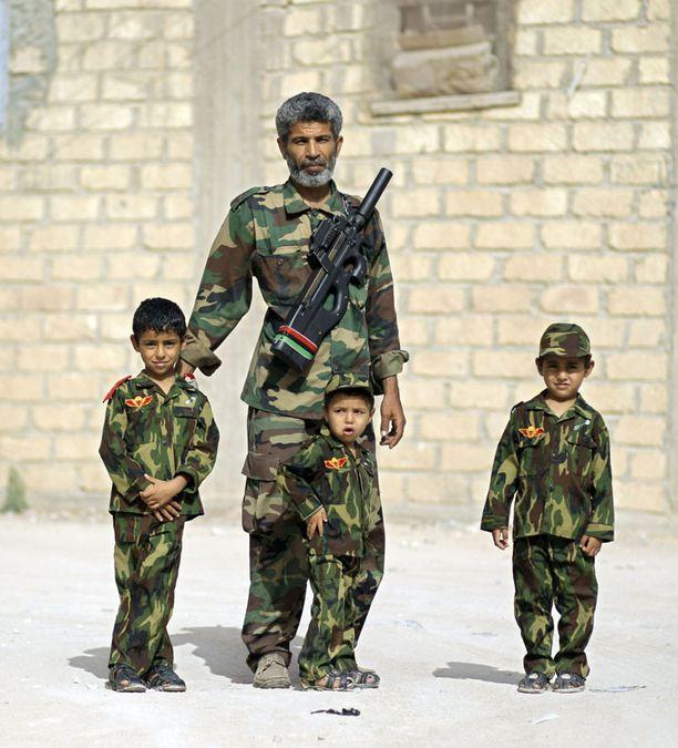 Kapinallinen Beshir Mahmoud, 45, poseerasi lastensa kanssa valokuvaajalle Ajdabiyassa lauantaina.