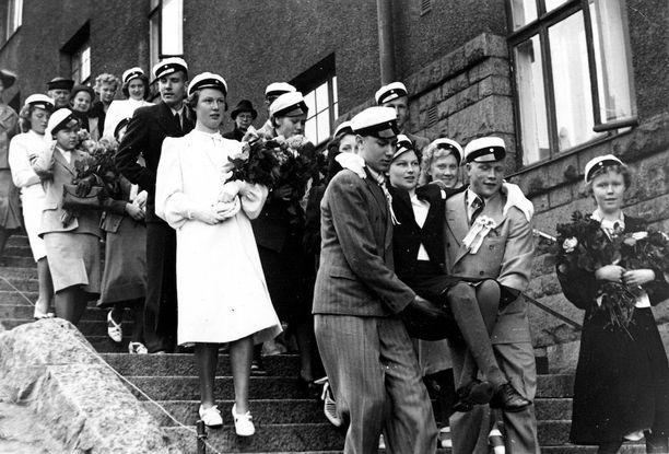 """Kallion yhteiskoulun ylioppilaat kantoivat """"jalkaviallisen"""" toverinsa Ässärykmentin patsaalle toukokuun lopussa 1941."""