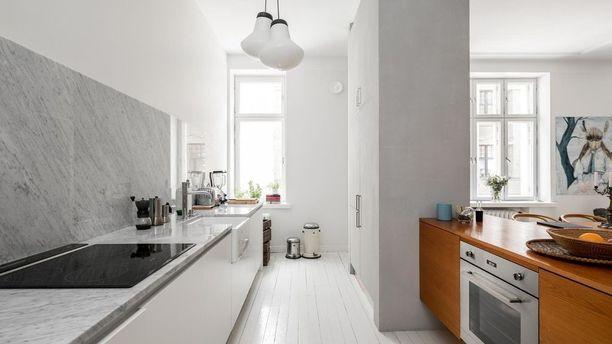 Ripaus luksusta! Tämän keittiön välitila on marmoria. Marmoripinta jatkuu keittiötasosta hauskasti seinälle.