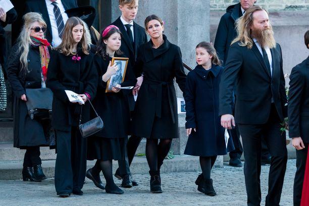 Leah, Maud, Märtha Louise ja Emma Ari Behnin hautajaisissa tammikuussa. Maud piteli käsissään isästä piirrettyä, kehystettyä kuvaa.